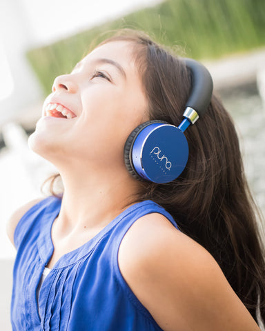 Little girl wearing blue Puro Sound headphones