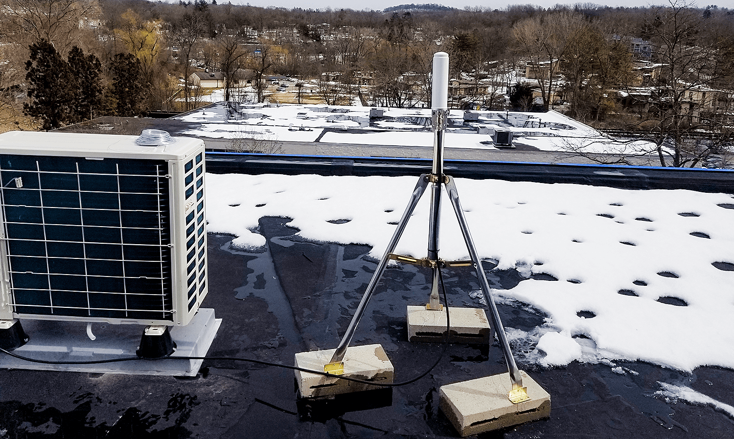 Top of 2 buildings showing exterior antenna installed on tripod