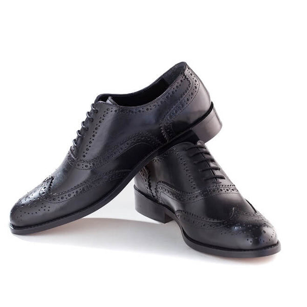 A side view of pair of men's handmade wingtip oxford brogue shoes made with black leather