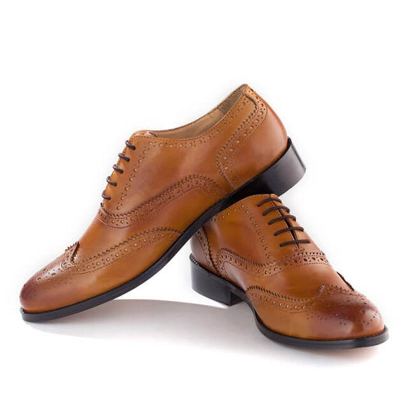 A side view of pair of men's handmade wingtip oxford brogue shoes made with tan leather