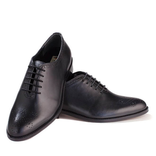 A front view of men's bespoke whole cut brogue shoes made with black leather