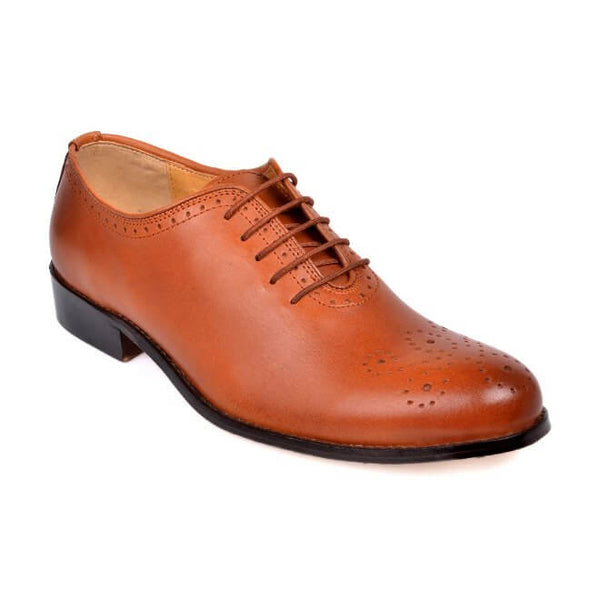 A side view of men's bespoke whole cut brogue shoes made with cognac leather