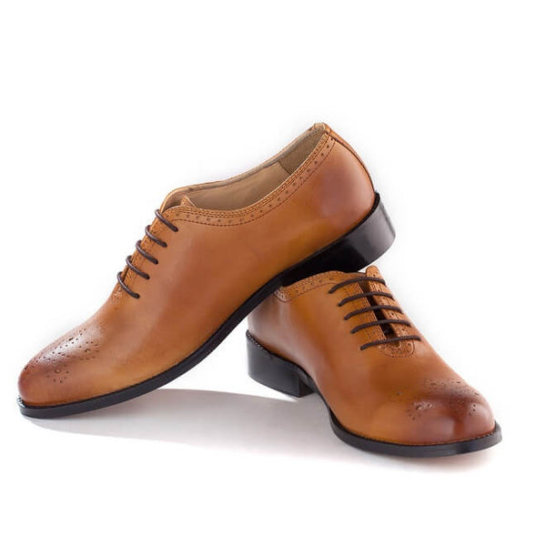 A side view of men's bespoke whole cut brogue shoes made with tan leather