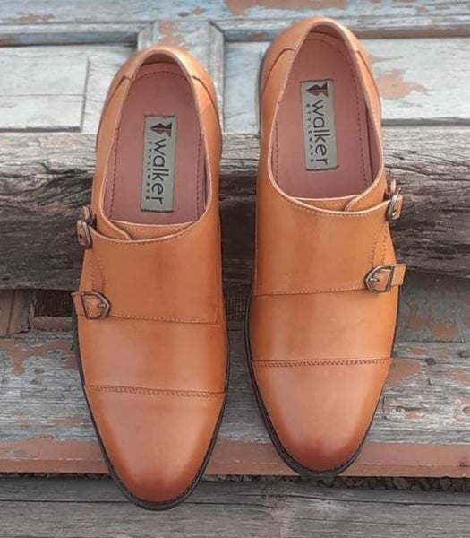 A top view of size 39 men's double monk strap shoes made with tan leather kept on wooden plank