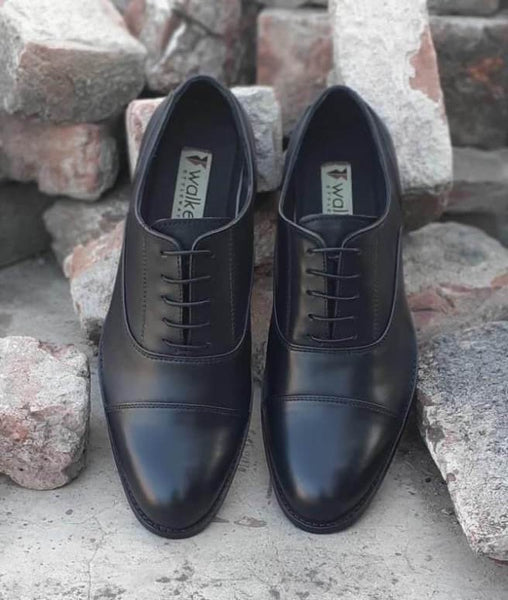 A top view of pair of men's bespoke cap toe oxford shoes made with black leather