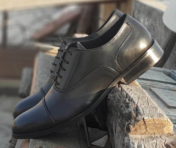A side view of pair of men's bespoke cap toe oxford shoes made with black leather