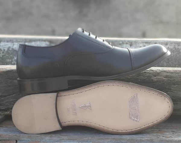 A sole view of pair of men's bespoke cap toe oxford shoes made with black leather