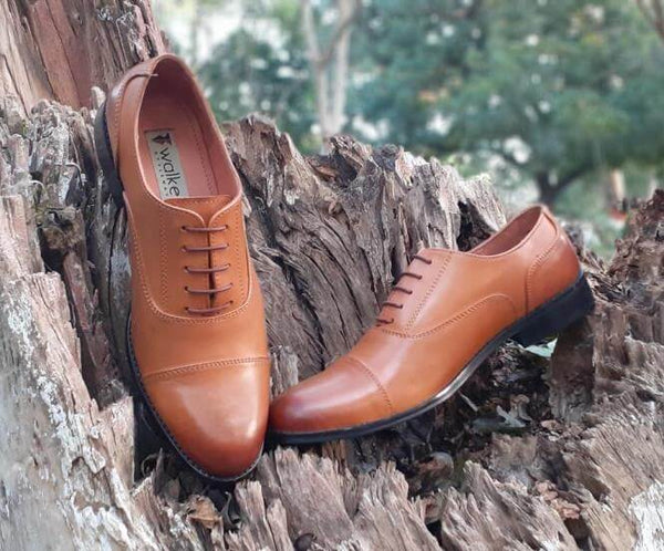 A front view of pair of men's bespoke cap toe oxford shoes made with tan leather
