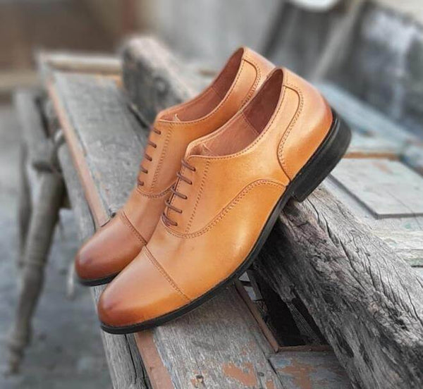 A side view of pair of men's bespoke cap toe oxford shoes made with tan leather kept on wooden plank