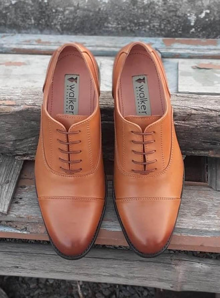 A top view of pair of men's bespoke cap toe oxford shoes made with tan leather