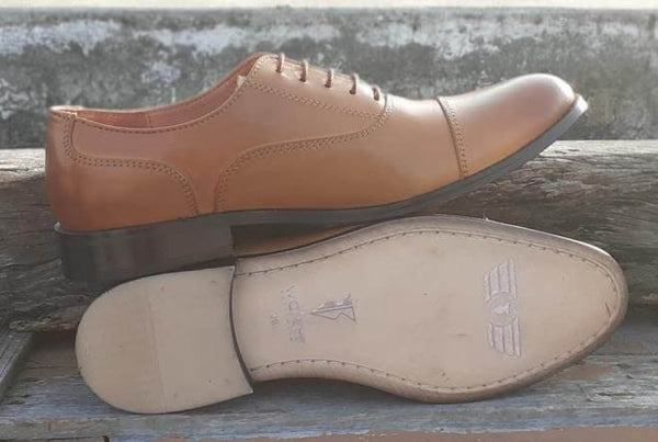 A sole view of pair of men's bespoke cap toe oxford shoes made with tan leather