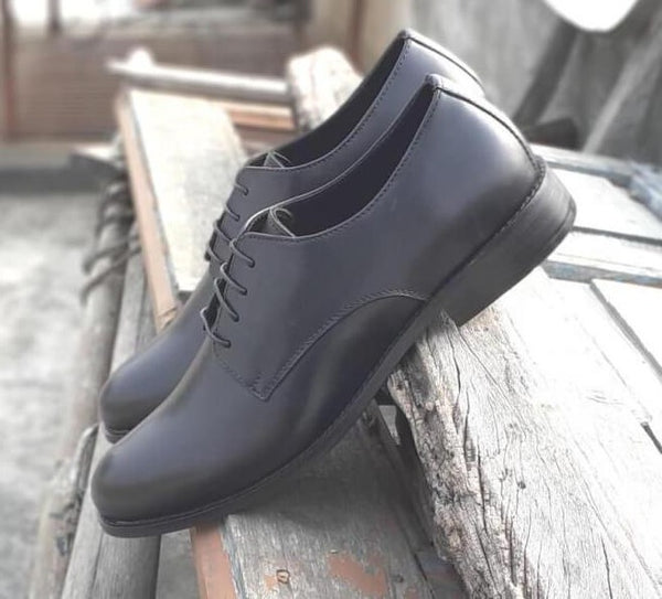 A side view of size 5 men's shoes made with black leather kept on wooden plank