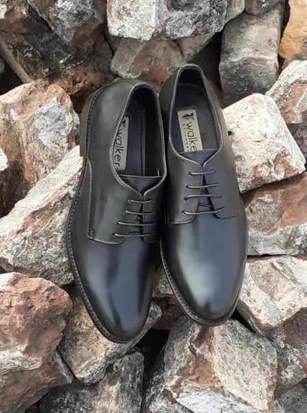 A top view of size 5 men's shoes made with black leather
