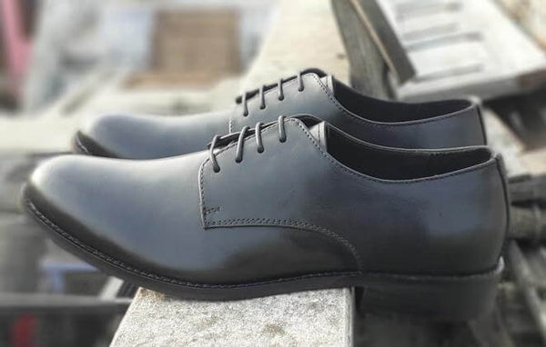 A side view of size 5 men's shoes made with black leather