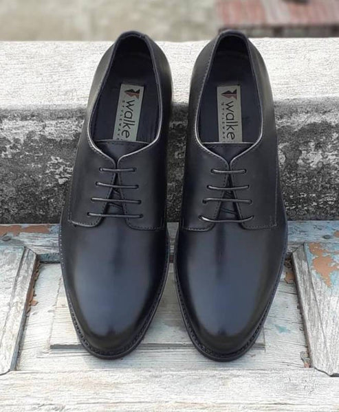 A top view of size 5 men's shoes made with black leather kept on wooden plank