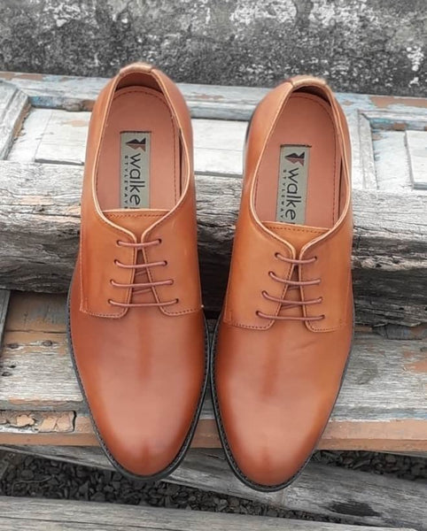 A top view of size 5 men's shoes made with cognac leather