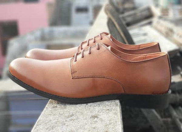 A side view of size 5 men's shoes made with cognac leather