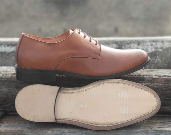 A sole view of size 5 men's shoes made with cognac leather