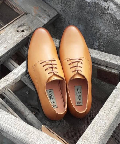 A top view of size 5 men's shoes made with tan leather kept on wooden chair