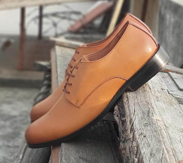 A side view of size 5 men's shoes made with tan leather