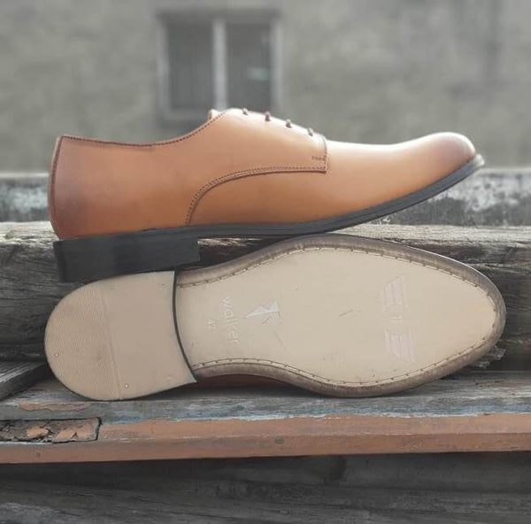 A sole view of size 5 men's shoes made with tan leather