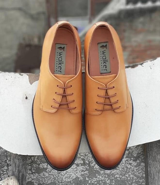 A top view of size 5 men's shoes made with tan leather