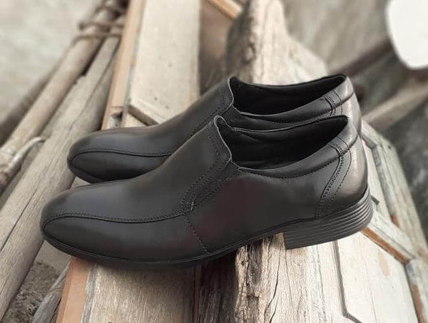 A side view of black leather men's slip-on big shoes showing stitching details