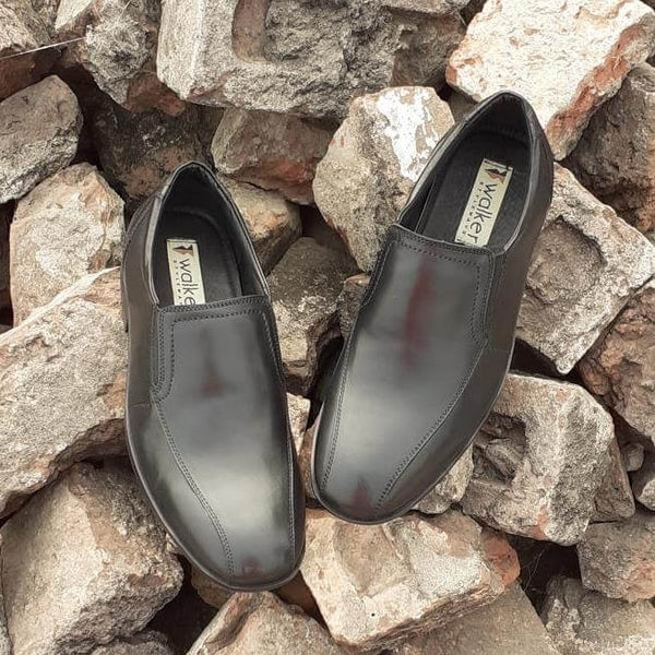 A top view of black leather men's slip-on big shoes kept on bricks