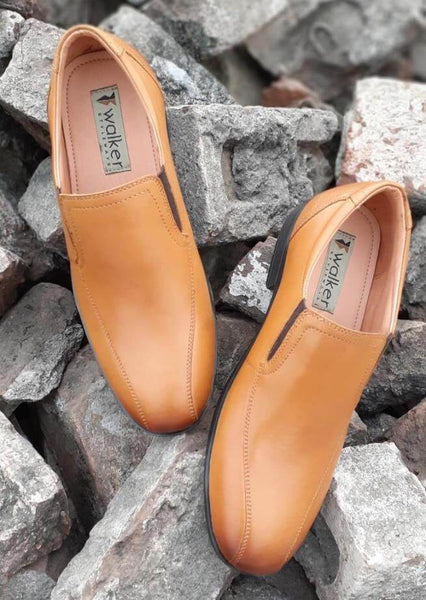 A top view of tan leather men's slip-on wide shoes kept on bricks