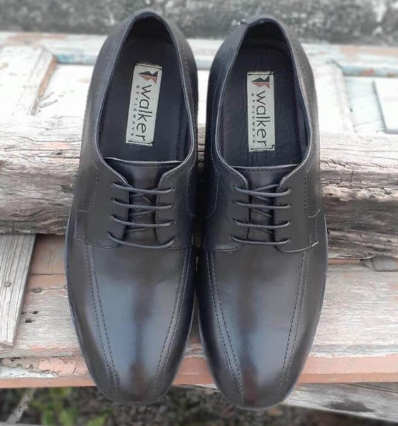 A front view of exclusive black leather men's wide shoes on wooden plank