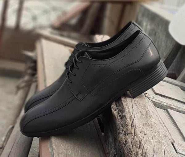 A side view of black leather men's wide shoes showing stitching details