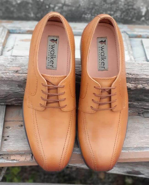 A top view of tan leather derby men's wide shoes on wooden plank