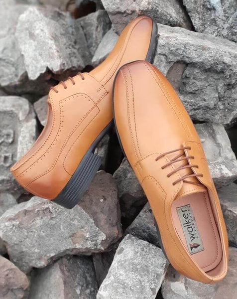 A top view of tan leather derby men's wide shoes kept on bricks