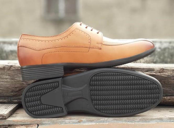 The sole side of tan leather men's wide formal shoes kept on wooden plank