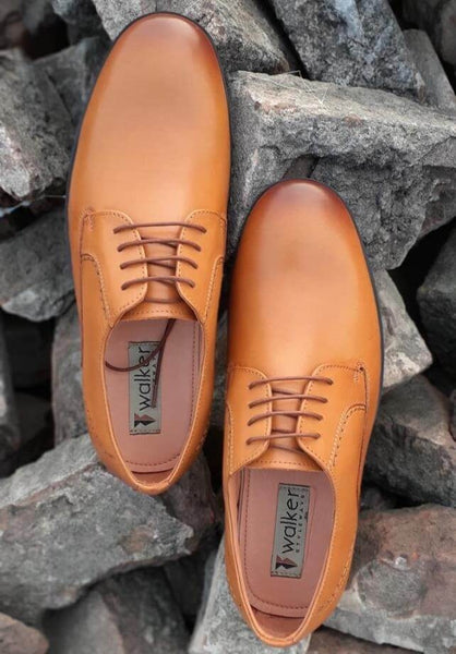 A top view of admirable tan leather derby big shoes on bricks