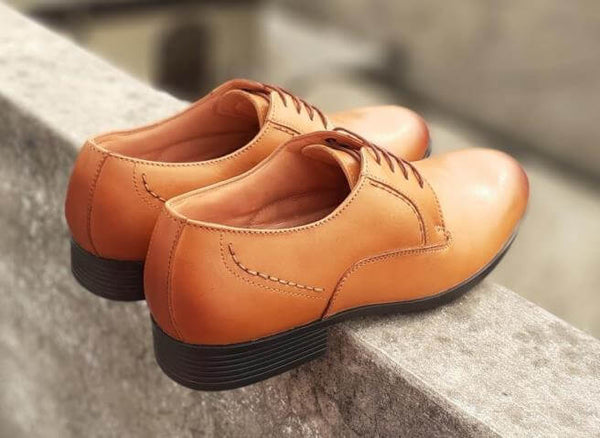 A side back view of admirable tan leather derby pair of big shoes