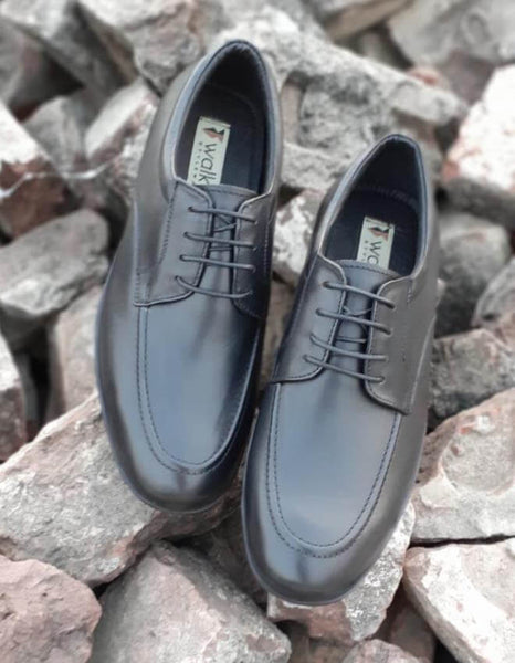 A top view of exceptional black leather derby wide shoes on bricks