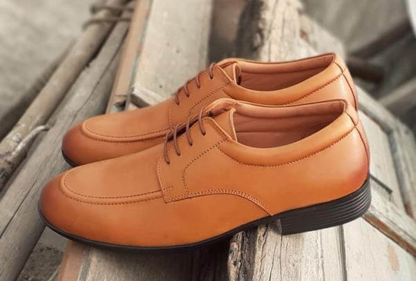A side top view of exceptional tan leather wide derby shoes