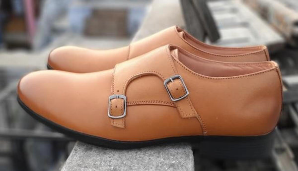 A side view showing stitching and buckle details of men's broad shoes