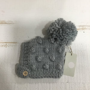 chunky knit winter hat for baby. Button under chin, multiple pompoms.