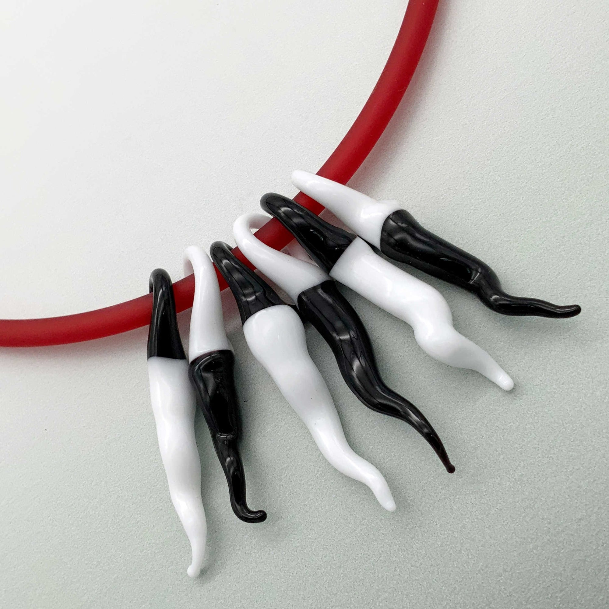 6 Piece black and white glass chilli necklace on a red PVC