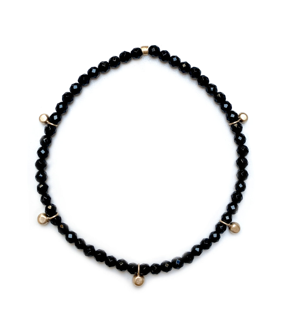 Gold bead charm stretch bracelet with black onyx faceted beads