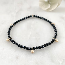 Load image into Gallery viewer, Gold bead charm stretch bracelet with black onyx faceted beads