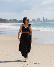 Photo of model on beach, wearing NOOZ Bali Jumpsuit, belted, in Black.