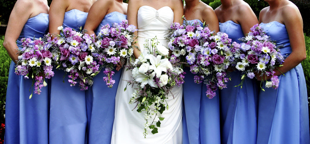 wedding showing bridesmaids in beautiful lilac blue strapless dress, girls holding bouquet of lilac purple flowers, bride is wearing white sweetheart strapless dress, holding pretty strap flowers