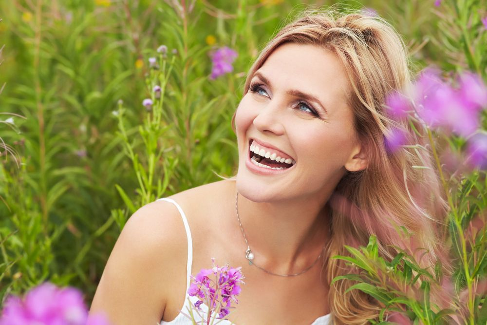 blonde woman in field of grass and flowers
