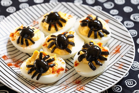 eggs with spiders made of olives on top