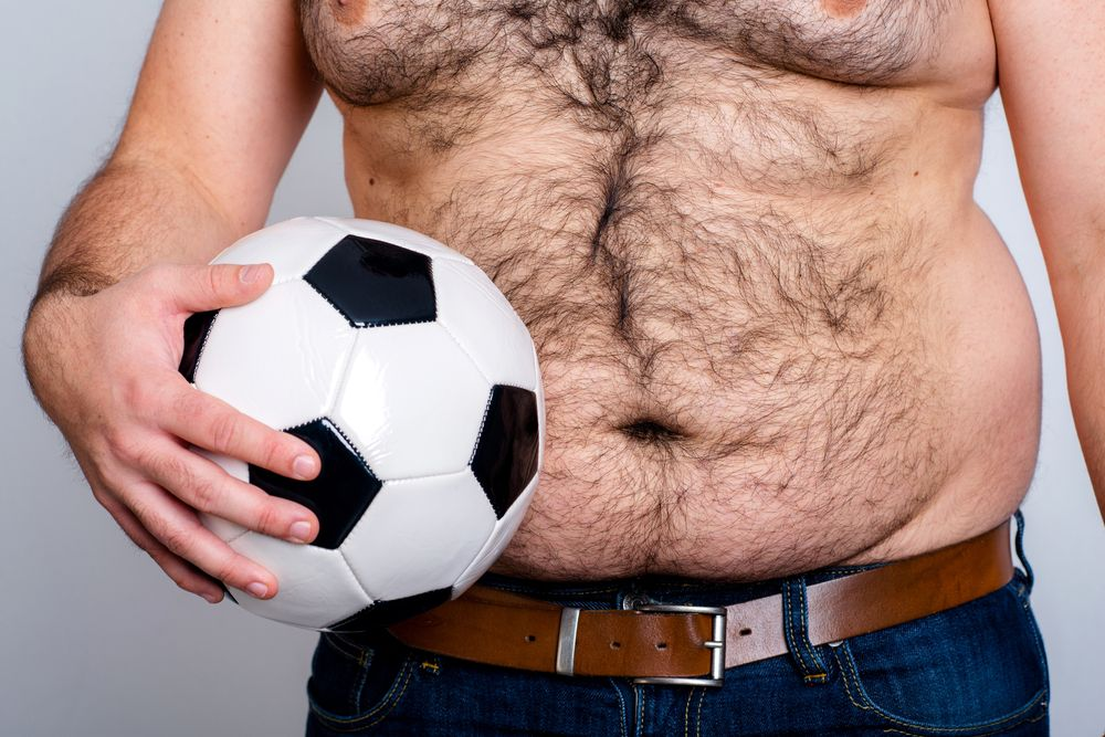 fat hairy man's body holding soccer ball in hand