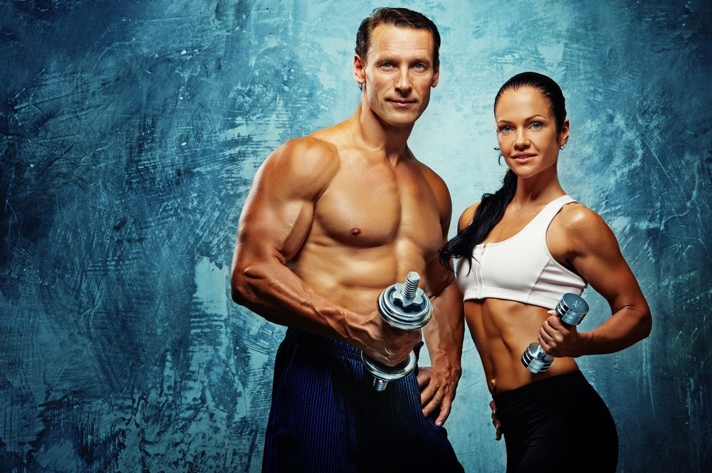 fitness couple holding dumbbells in front of blue background