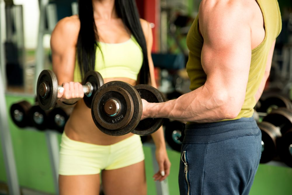 fitness couple with weights in gym